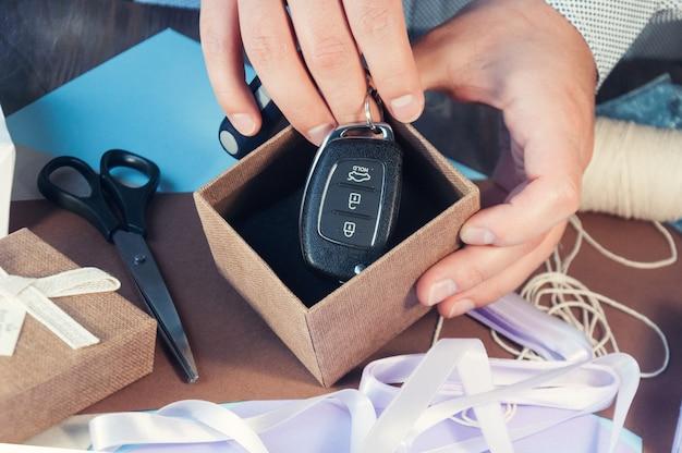 Um homem em uma camisa leve está preparando uma caixa de presente para o feriado. tonificação o carro como presente. chaves do carro na caixa de presente.