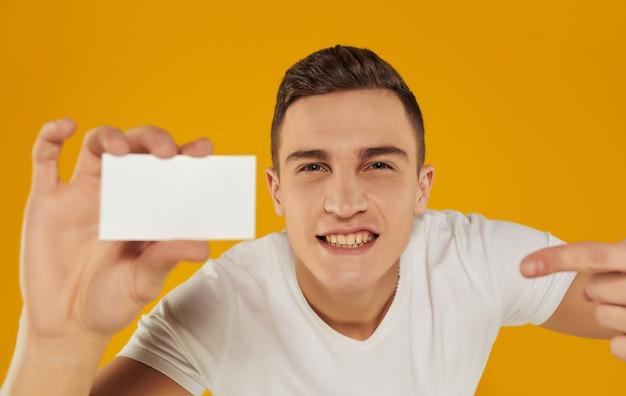 Um homem em uma camiseta branca com um cartão de visita nas mãos em um fundo amarelo. foto de alta qualidade
