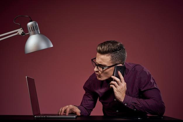 Um homem em uma camiseta branca com um laptop e um tablet eletrônico trabalha à mesa