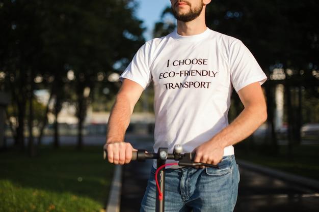 Um homem em uma camiseta branca segura os braços de sua scooter elétrica enquanto montava na superfície borrada do parque