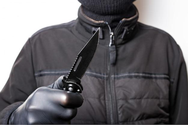 Um homem em uma jaqueta preta com uma faca em uma parede branca assalto ou crime com uma faca.