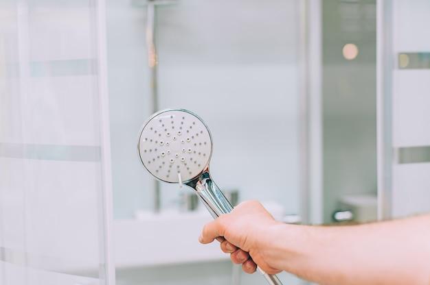 Um homem em uma loja de ferragens escolhe uma cabine de duche para sua casa.