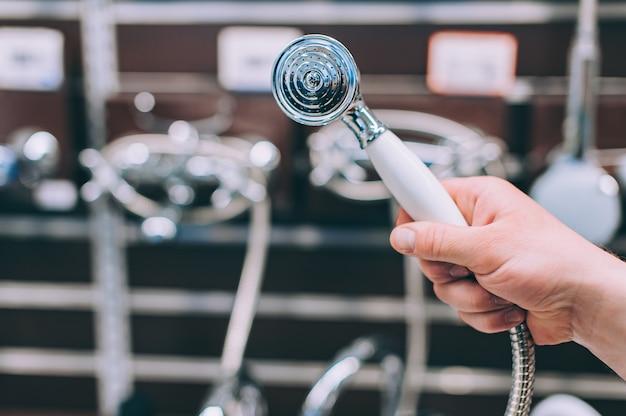 Um homem em uma loja de ferragens escolhe uma torneira para um chuveiro.