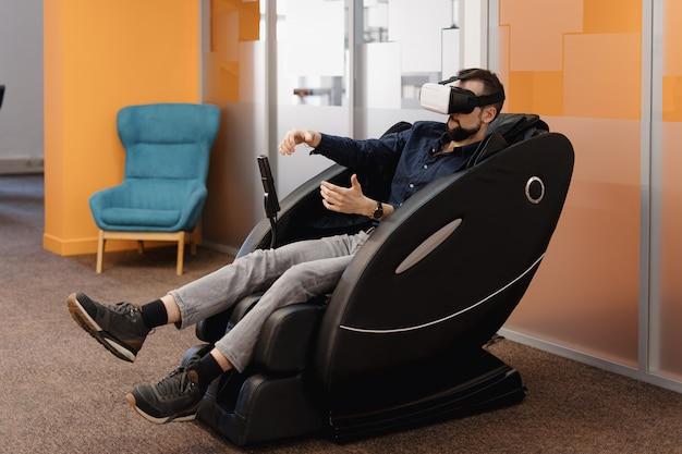 Um homem em uma poltrona de massagem usando a tecnologia vr