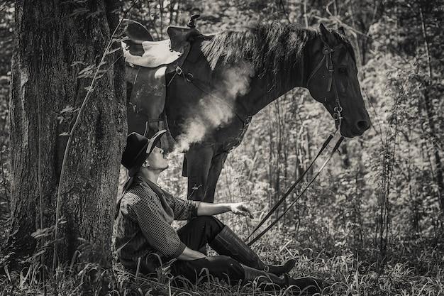 Um homem em uma roupa de cowboy com seu cavalo