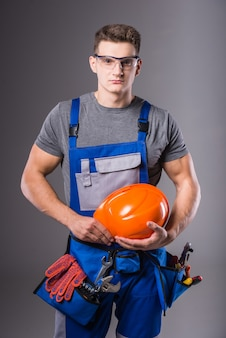 Um homem em uma roupa está de pé com um capacete nas mãos.