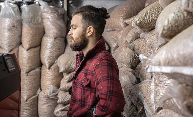 Um homem em uma sala com uma caldeira de combustível sólido, trabalhando com biocombustível, aquecimento econômico.