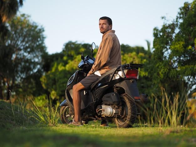 Um homem em uma scooter está sentado assistindo o pôr do sol. ambiente tropical. viajando em um ciclomotor.