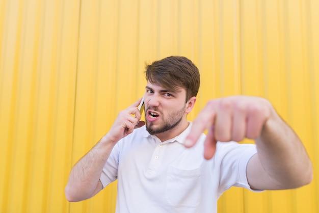 Um homem emocional chama o telefone, irritado