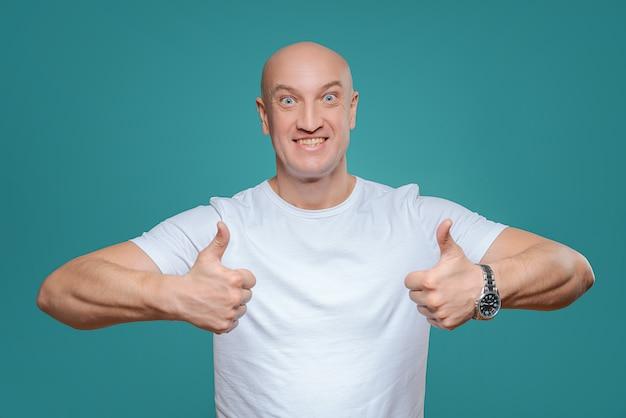 Um homem emocional em uma camiseta branca mostra com um gesto de mão que tudo é legal