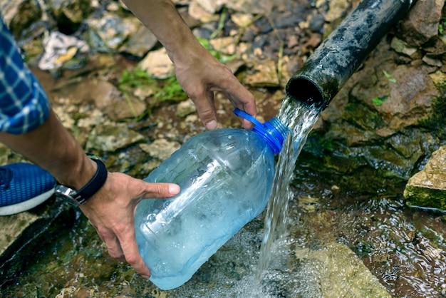 Um homem enche uma garrafa de plástico com água de uma fonte subterrânea de água limpa