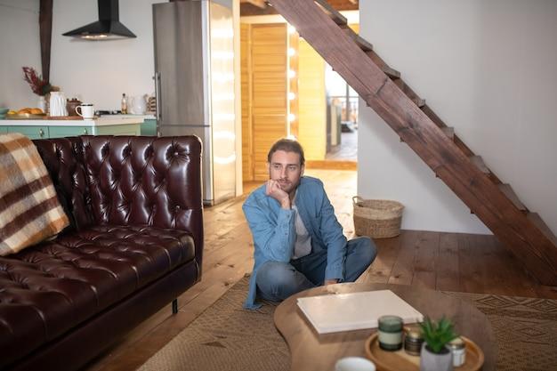 Um homem entediado sentado no chão de seu apartamento