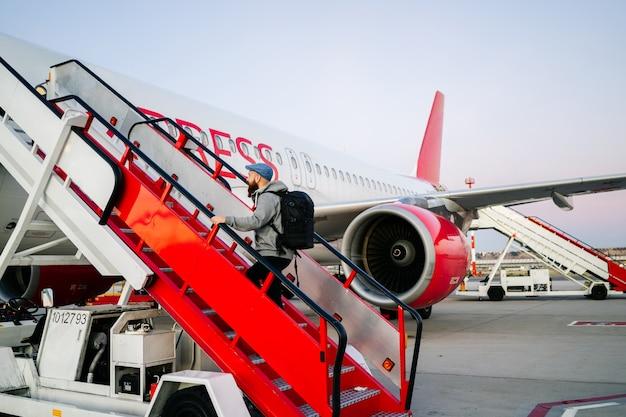 Um homem entra no avião da pista descendo as escadas
