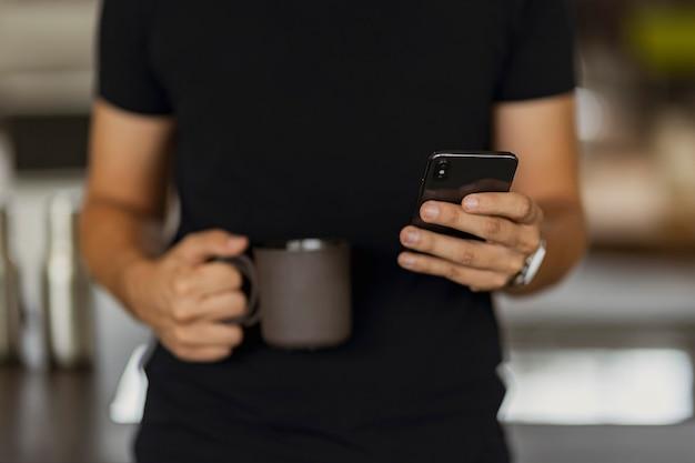 Um homem enviando uma mensagem de texto em seu telefone enquanto segura uma xícara de café preto na outra mão