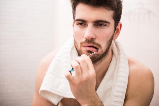 Um homem escova os dentes no banheiro