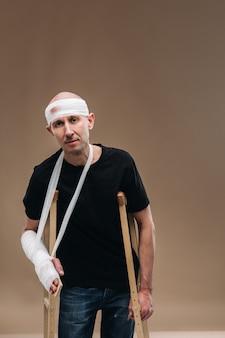 Um homem espancado, com a cabeça enfaixada e um braço engessado, está de pé com muletas em um fundo cinza.