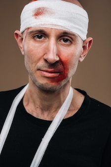 Um homem espancado com uma bandagem na cabeça e um gesso no braço está em um fundo cinza