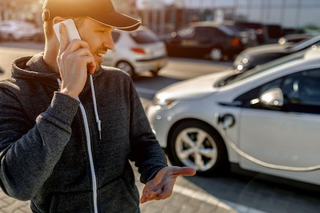 Um homem espera enquanto seu carro elétrico carrega em um carregador em um estacionamento perto de um shopping center.