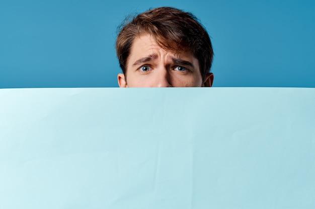 Um homem espiando por trás de um banner de publicidade em close-up