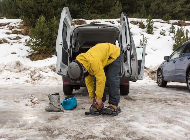 Um homem esportivo calçando suas raquetes de neve para iniciar uma excursão nas montanhas nevadas.