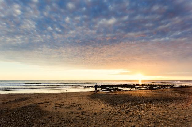 Um homem está assistindo a um belo pôr do sol sobre o mar mediterrâneo em pé perto da costa