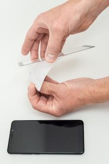 Um homem está colando um vidro protetor na tela de um smartphone