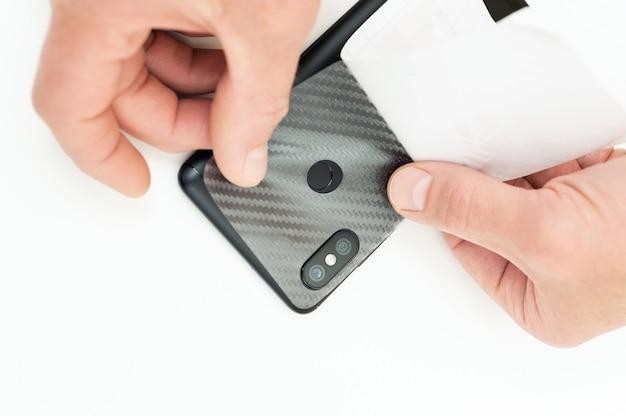 Um homem está colando uma película protetora de carbono no smartphone.