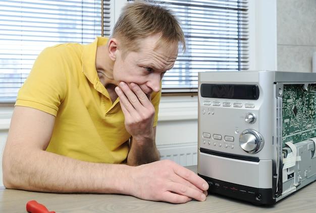 Um homem está consertando o sistema musical. ele está olhando dentro do dispositivo.