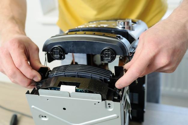 Um homem está consertando o sistema musical. ele está puxando o cd changer para fora.