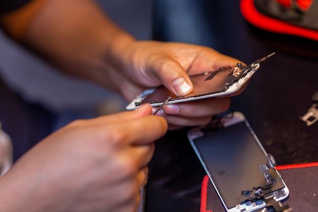 Um homem está consertando um telefone celular