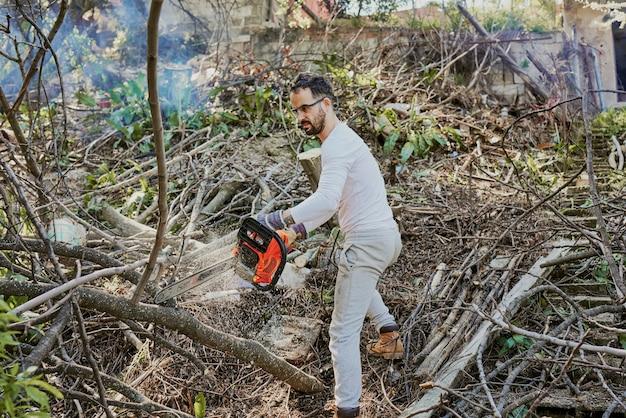 Um homem está cortando os galhos de uma árvore caída na floresta.