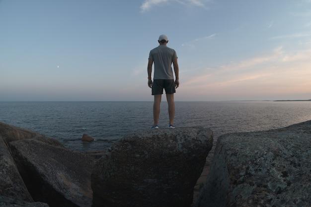 Um homem está de pé em um penhasco de pedra perto da costa do mar. vista traseira