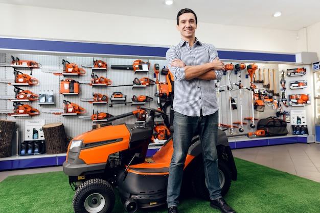 Um homem está de pé perto de um cortador de grama.