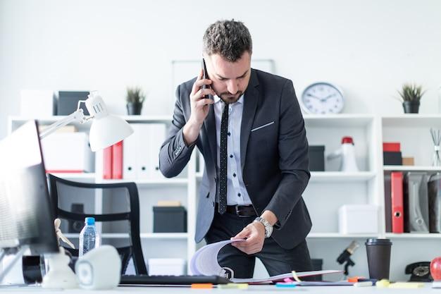 Um homem está de pé perto de uma mesa no escritório, falando ao telefone e folheando os documentos.