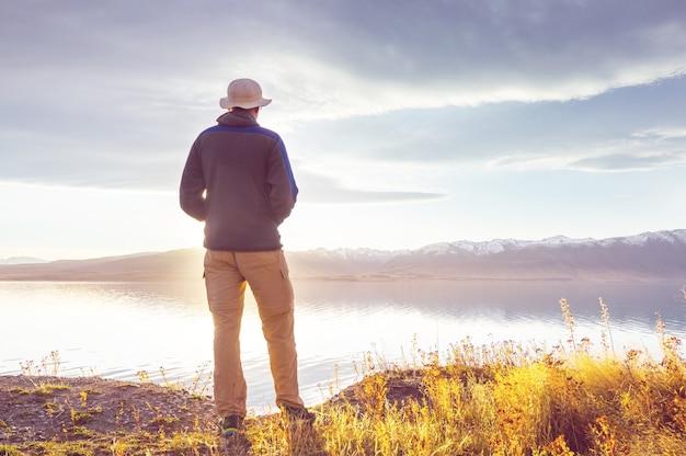Um homem está descansando à vontade à beira do lago calmo. férias relaxantes