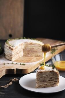 Um homem está despejando mel em uma fatia de bolo em um prato. bolo de panqueca com creme de leite, decorado com açúcar de confeiteiro e raminhos de tomilho. sobremesa em uma grande placa de madeira. prato em uma velha mesa de cozinha rústica.