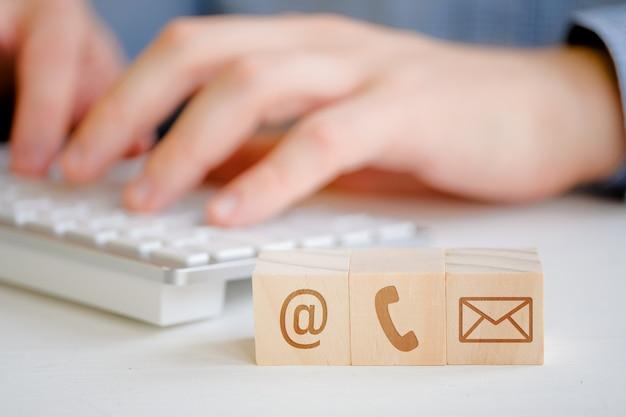 Um homem está digitando em um teclado ao lado de cubos de madeira com um símbolo de e-mail, telefone e carta. contato para comunicação.