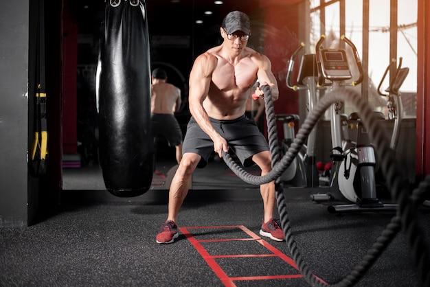 Um homem está exercitando com corda no ginásio