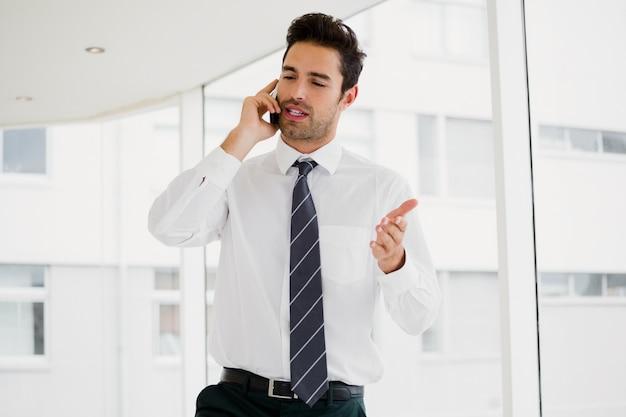 Um homem está falando ao telefone e gesticulando
