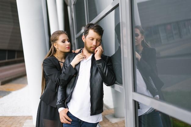 Um homem está falando ao telefone, uma garota está abraçando um homem