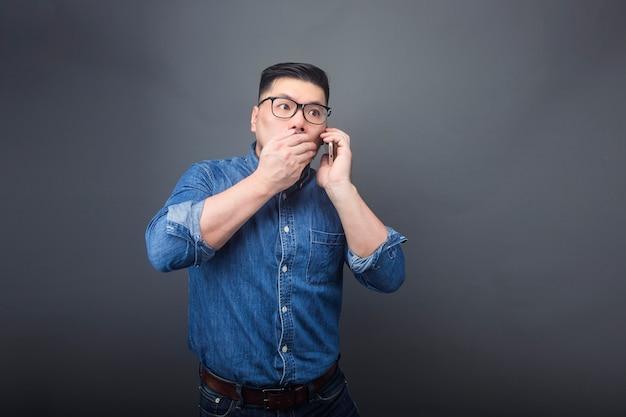 Um homem está fazendo um telefonema com uma expressão de surpresa.