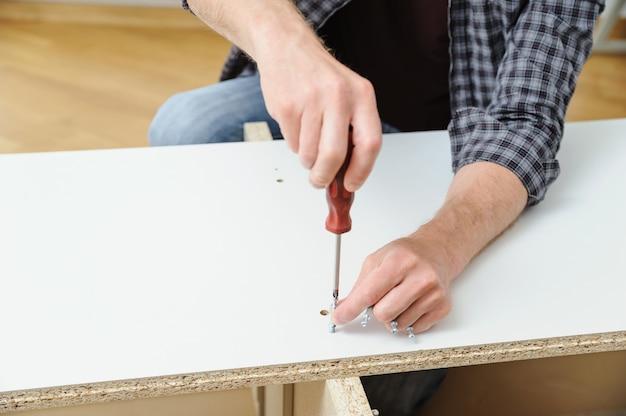 Um homem está instalando parafusos de conexão conjunta na placa da mobília.