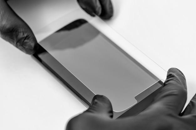 Um homem está instalando um vidro protetor na tela de um smartphone.