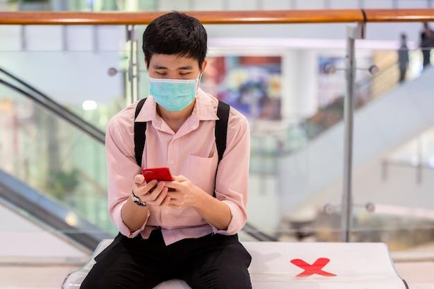 Um homem está jogando um smartphone enquanto está sentado em um banco de shopping center com sinais de cautela de distanciamento social. (foco seletivo)
