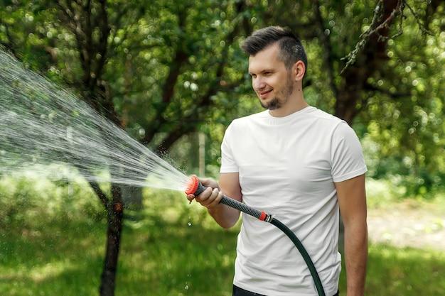 Um homem está molhando de uma mangueira