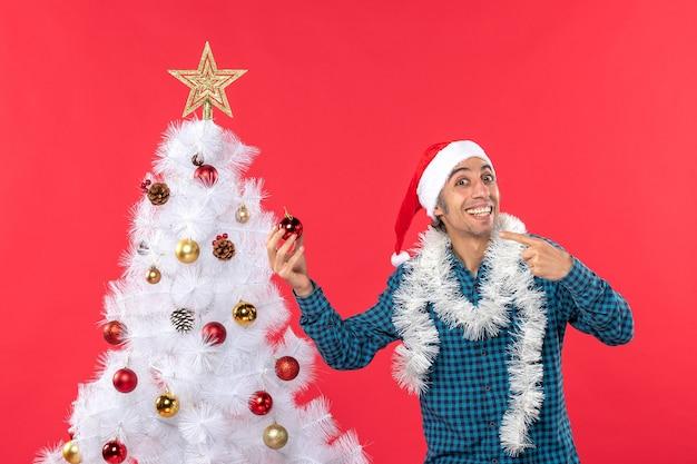 Um homem está parado ao lado da árvore de natal