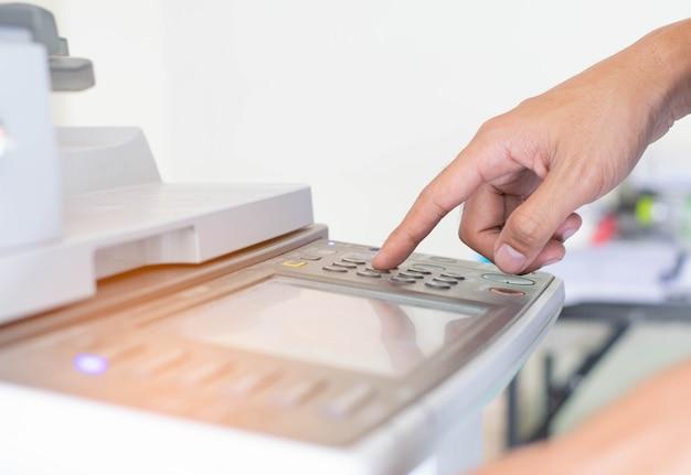 Um homem está pressionando o botton da impressora