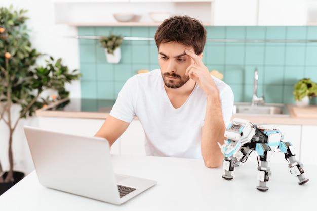 Um homem está programando um robô na cozinha