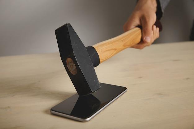 Um homem está quebrando um smartphone deitado na mesa de madeira com um grande martelo