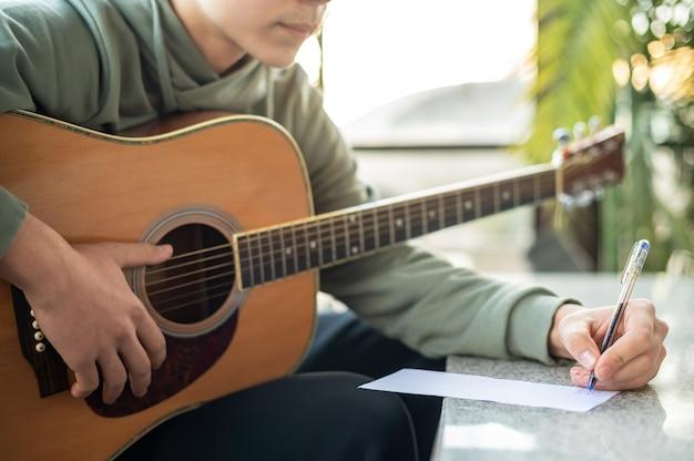 Um homem está segurando o violão e escrevendo algo em um caderno
